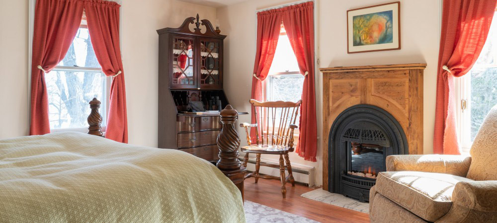 Orange curtains frame tall windows next to writing desk with curio cabinet and fireplace with high mantle.