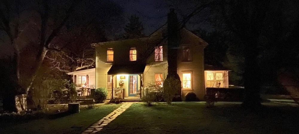 Exterior view of house at night with lights burning in every room, shining brightly against the dark contrast of night.