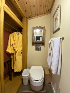 white toilet with garbage can beside, closet with yellow robe hanging, towel rack with white towels