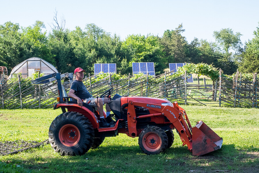 farmer relaxing on a red tractor in front of an extensive garden and solar panels