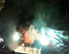 Boy Blowing out candles on a cake in the dark