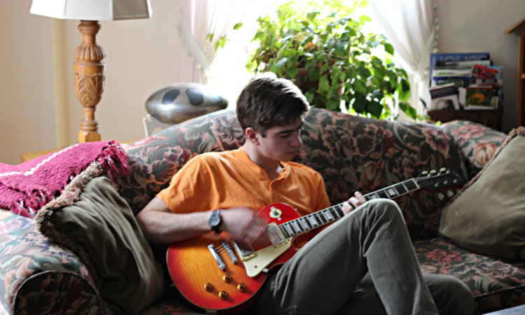 young man in orange shirt playing guitar on sofa in parlor