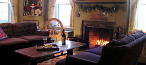 fireplace with fire light, wine bottle and glasses on table, spinning wheel in front of window