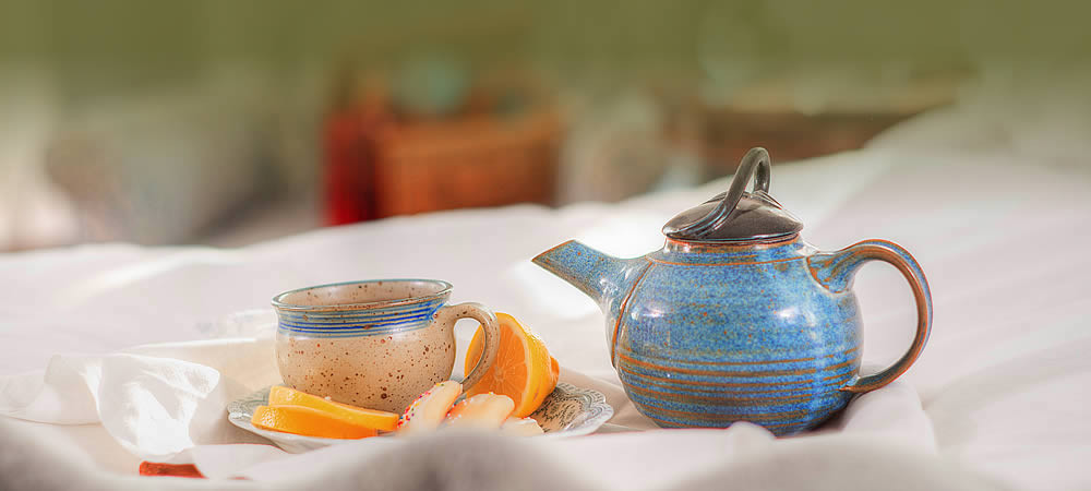 Small blue ceramic tea-pot with a matching teacup on a plate with fresh orange slices.