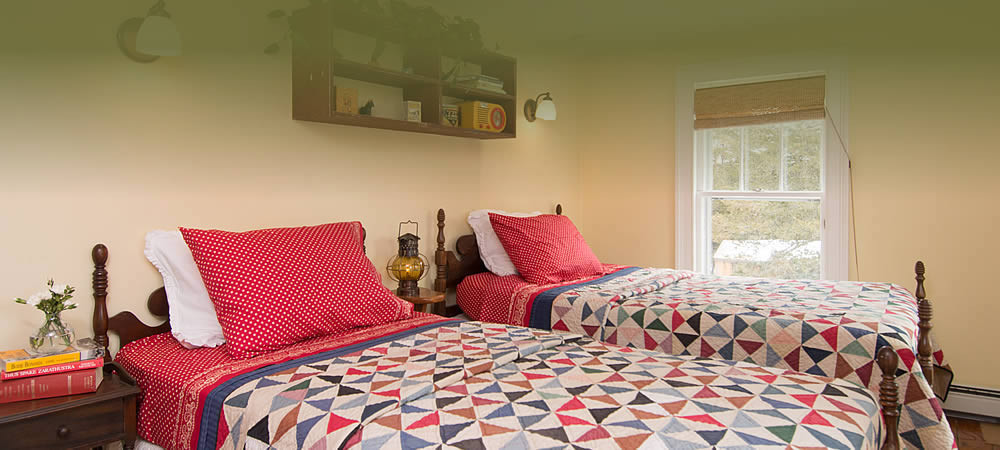 Two twin beds with brightly colored quilts and red plaid sheets in a room with bright windows and vintage sconces.