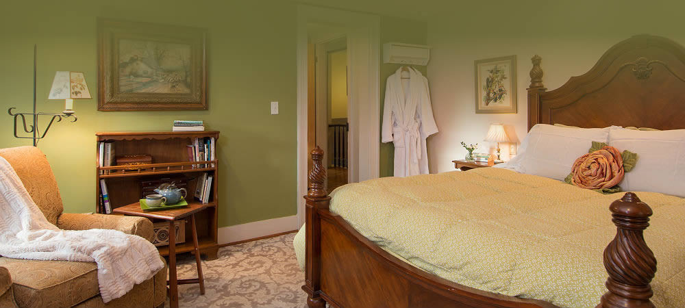 four poster bed with cream linens, a comfortable lounge chair and a white robe hanging from the back of the door.
