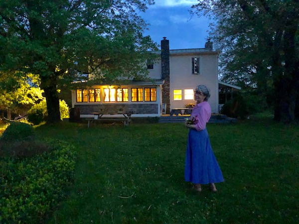 Spring Evening photo of farmhouse lit up and woman walking in the foreground
