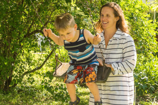 young mother pushing son on a swing with bushes behind them