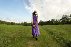 woman in purple dress strolling all by herself in a grassy meadow