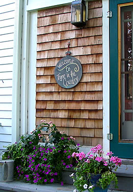 """Green front door with cedar shake siding surrounds and a sign that says """"welcome to Thyme in the country."""""""