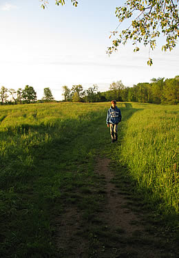 A man walking along a worn path through a large grassy field with the sun setting and casting a shadow.