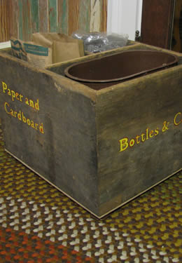 "A vintage recycling bin made of wood and stamped with the words ""paper and cardboard"" and ""bottles and cans""."