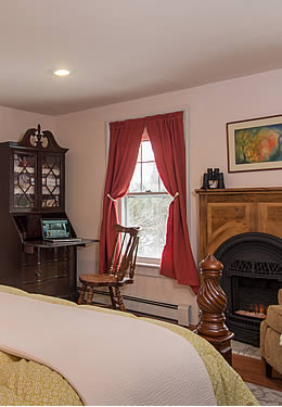 Neatly made bed facing a fireplace, a comfortable lounge chair and an antique writing desk.