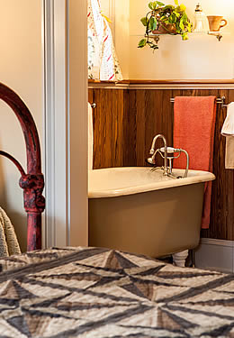 A large bed made with a grey patterned quilt, facing into a bathroom with a clawfoot tub.