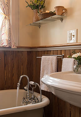 Bathroom with a clawfoot tub, a white pedistal sink and wood paneling.