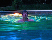 man swimming in a pool at night